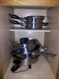 "#8- The side cabinet was repurposed for pots and pans as they fit better in here and are much more easily reached. The shelf that was removed from our glass/mugs cabinet, found on ""Paring Down Part 1, was added here for better organization."